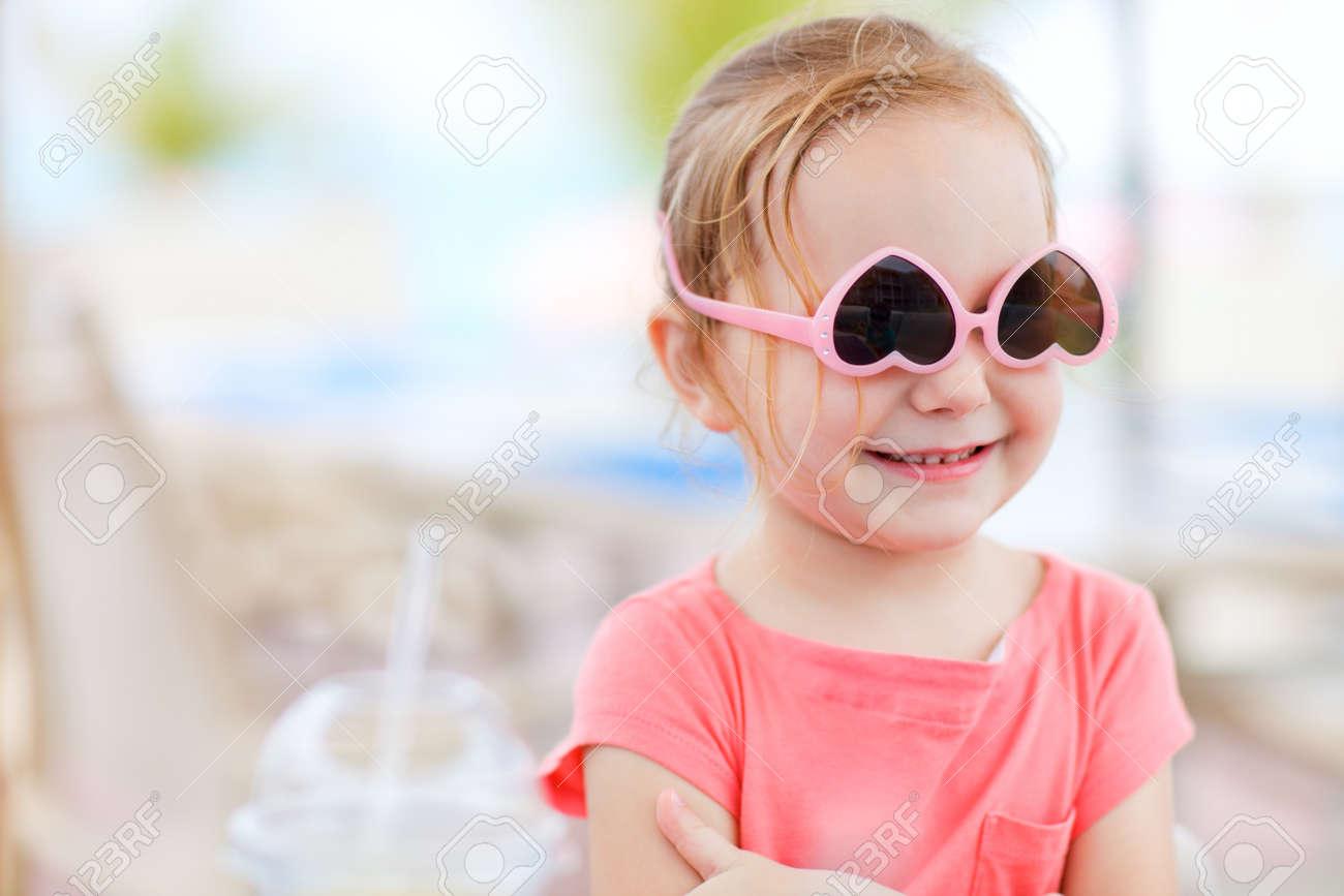a3268cafa8 Banque d'images - Portrait d'une petite fille mignonne avec des lunettes de  soleil à l'envers