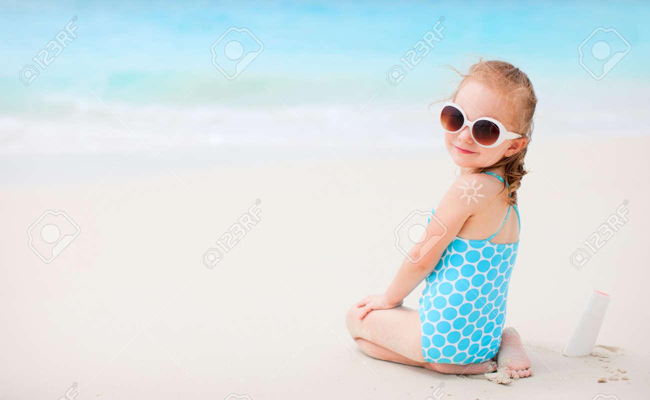 Banque d images - Petite fille à la plage avec de la crème solaire en forme  de son dos 301cdb9c7b8