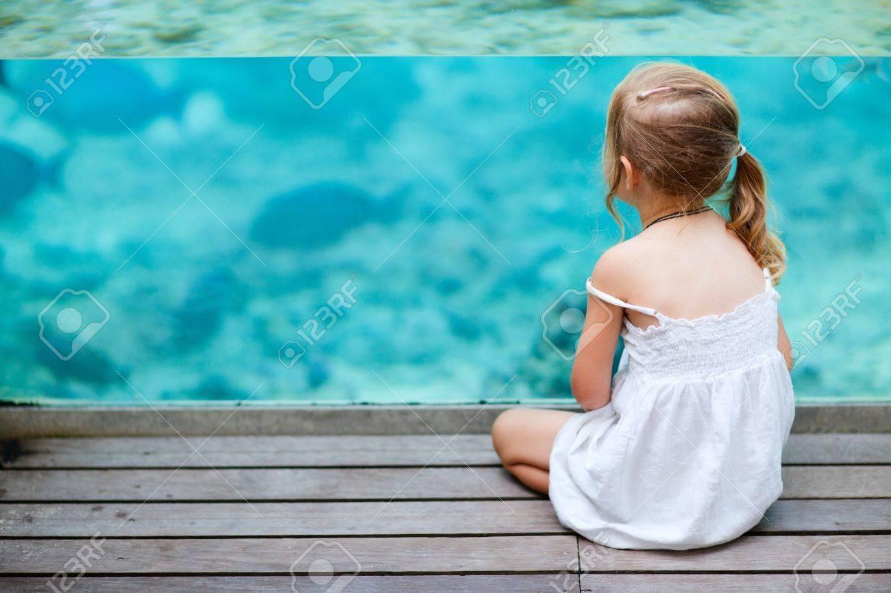 Little girl enjoying underwater sea life through glassed wall Stock Photo - 15810762