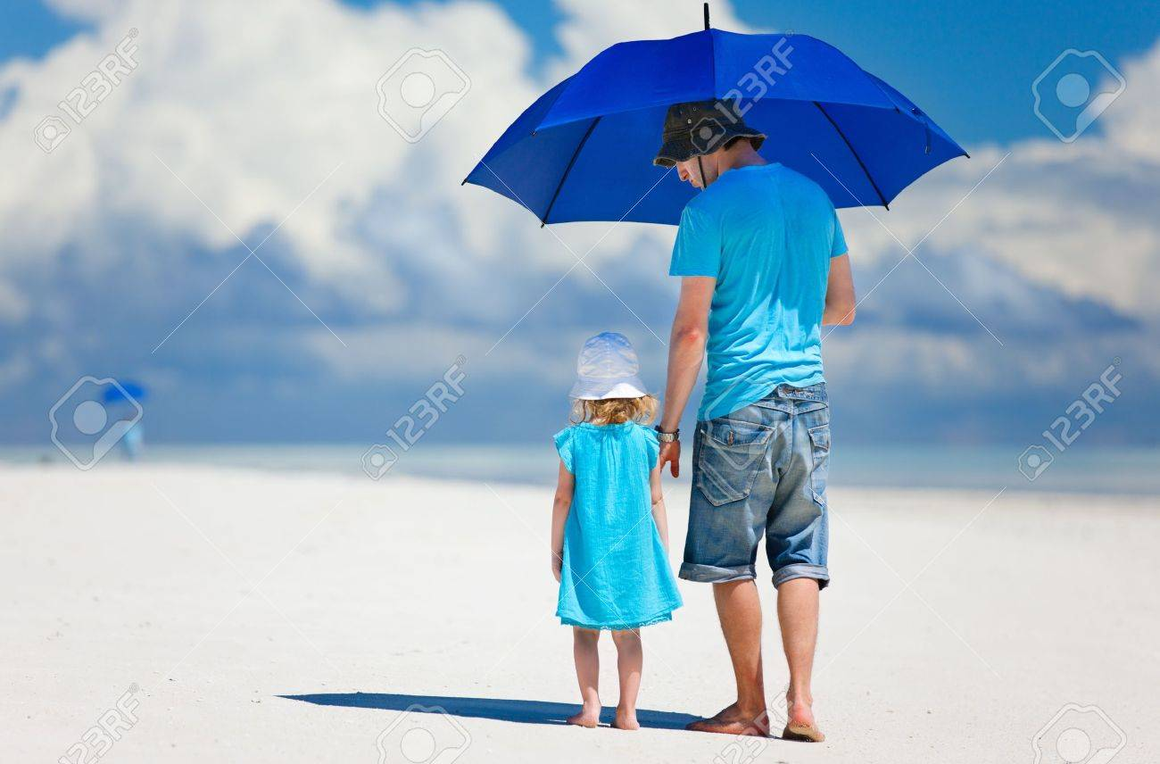 Father and daughter at beach with umbrella to hide from sun - 15892614