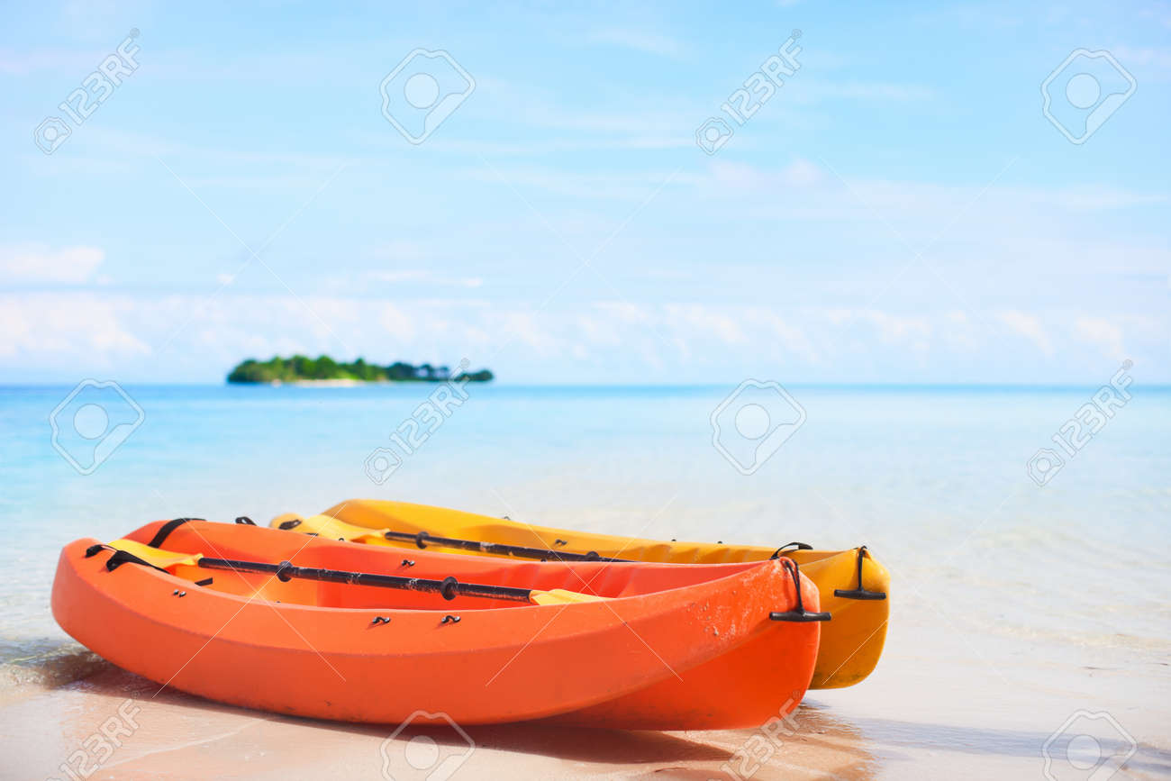 Two kayaks at tropical beach in front of small uninhabited island Stock Photo - 16318691