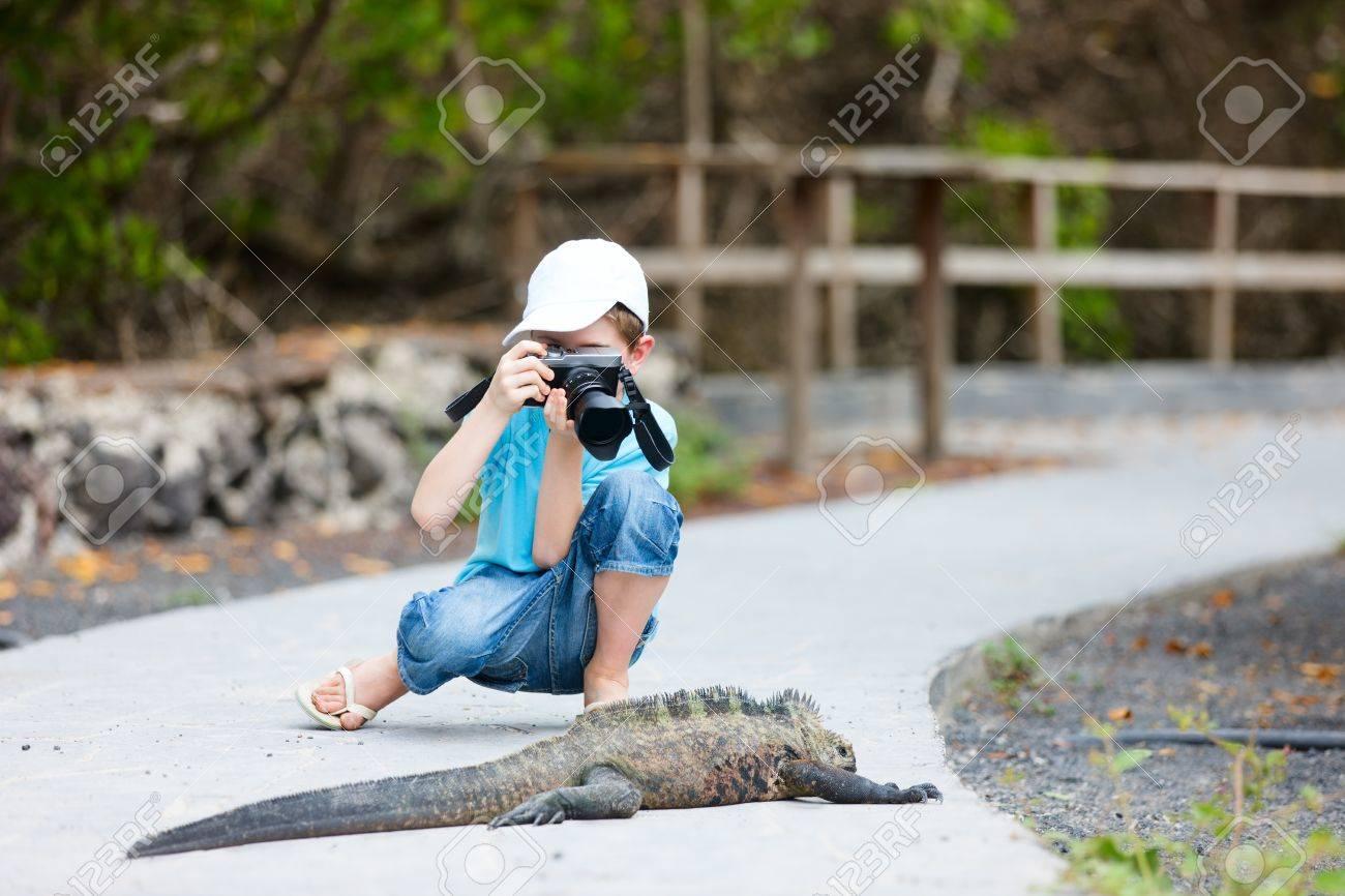 Little boy photographing huge marine iguana Stock Photo - 17603601