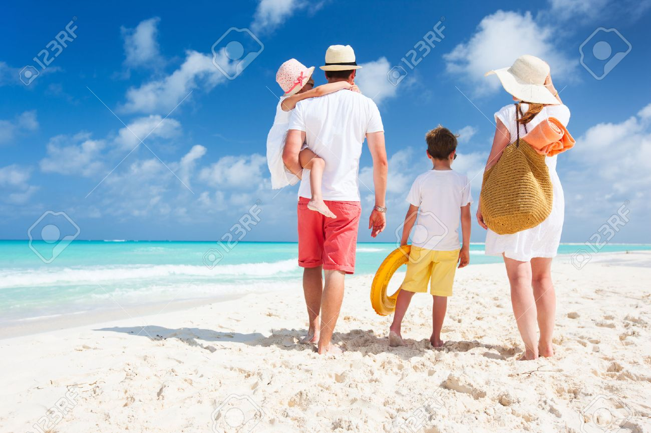 Back view of a happy family on tropical beach Stock Photo - 22997417