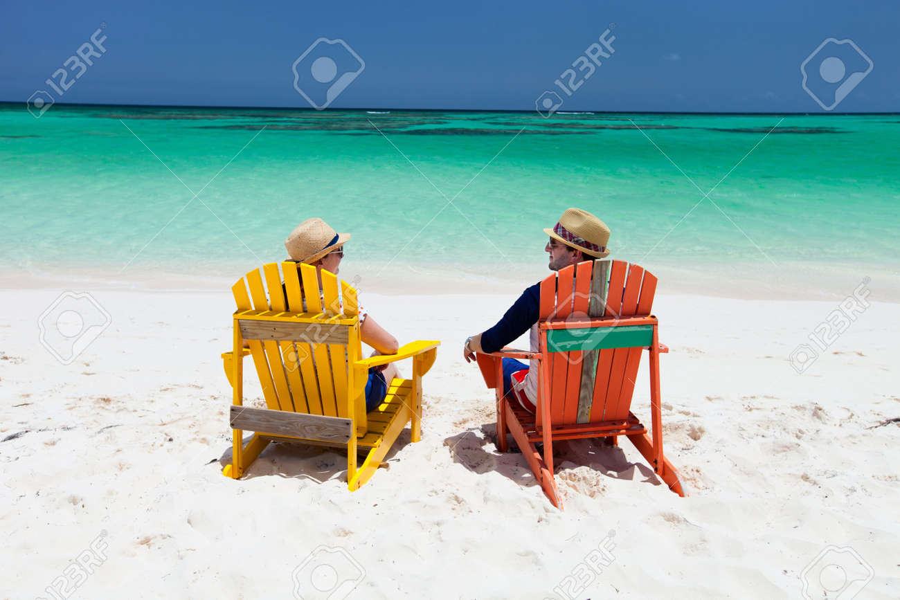 Happy couple sitting on colorful adirondack chairs at tropical..