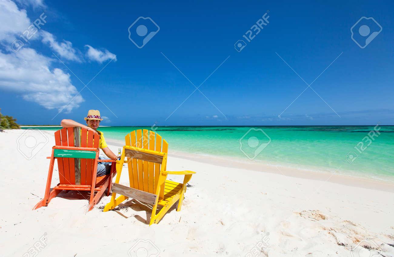 Giovane uomo godendo le vacanze in spiaggia tropicale con due ...