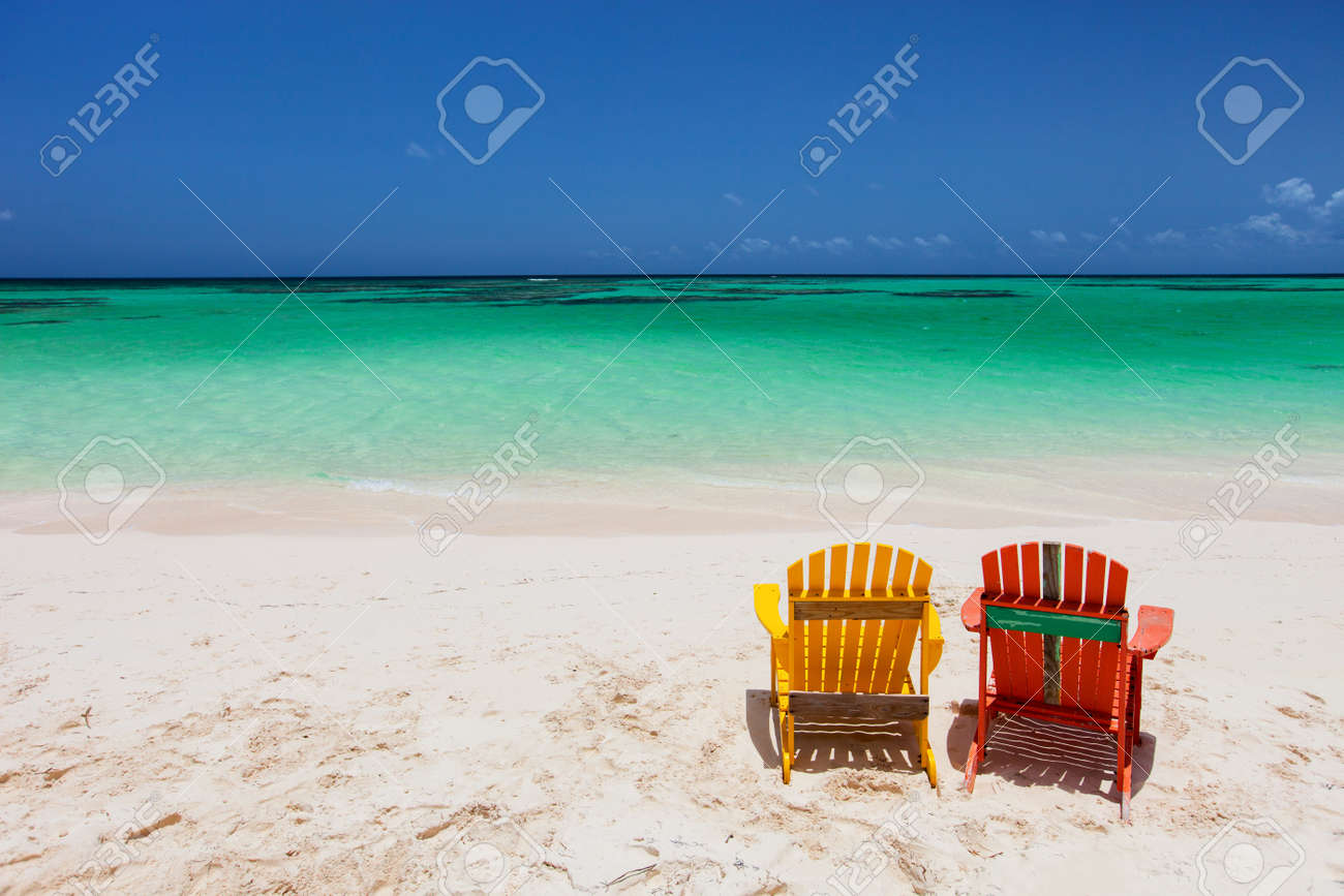 Colorful adirondack yellow and orange lounge chairs at tropical..