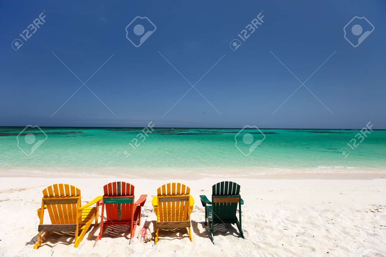 Row of colorful adirondack wooden chairs at tropical white sand..