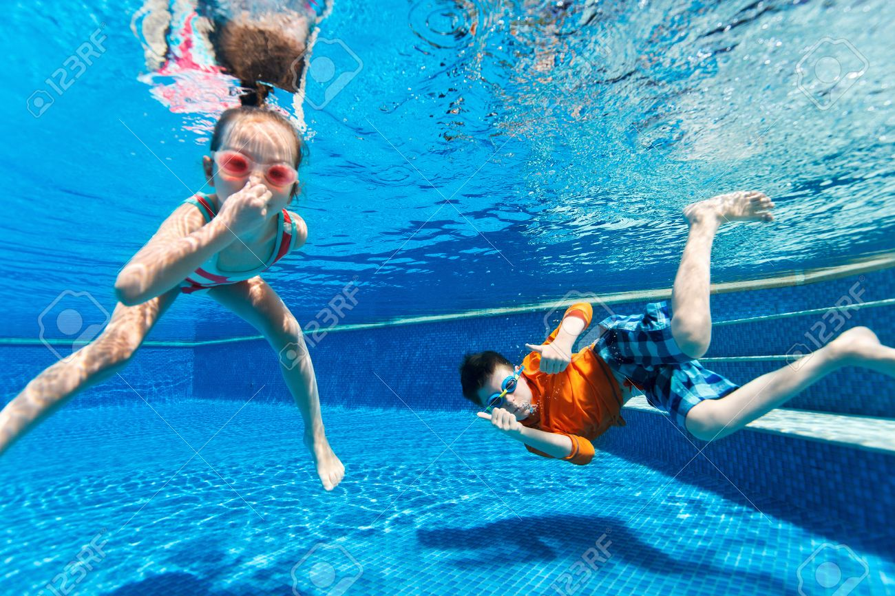 Kids having fun playing underwater in swimming pool on summer..