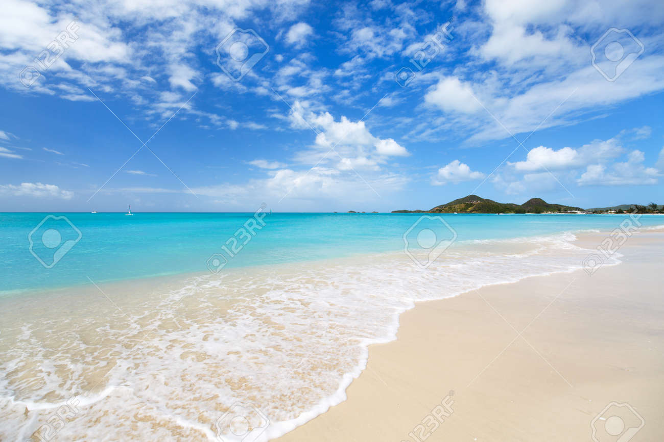 Idyllic tropical beach with white sand, turquoise ocean water and blue sky at Antigua island in Caribbean - 55732633