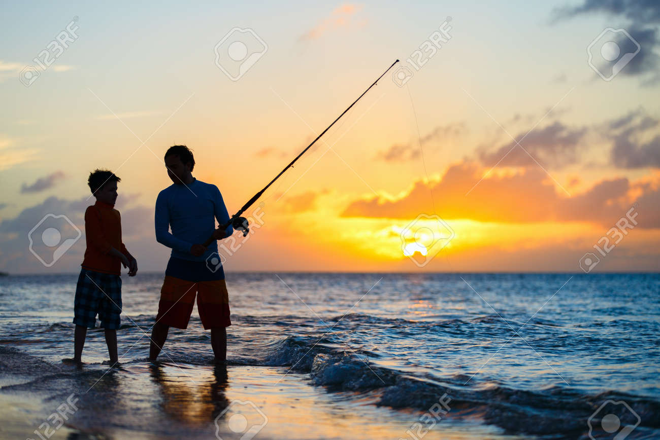 Father and son fishing together in ocean from beach on sunset - 55732536