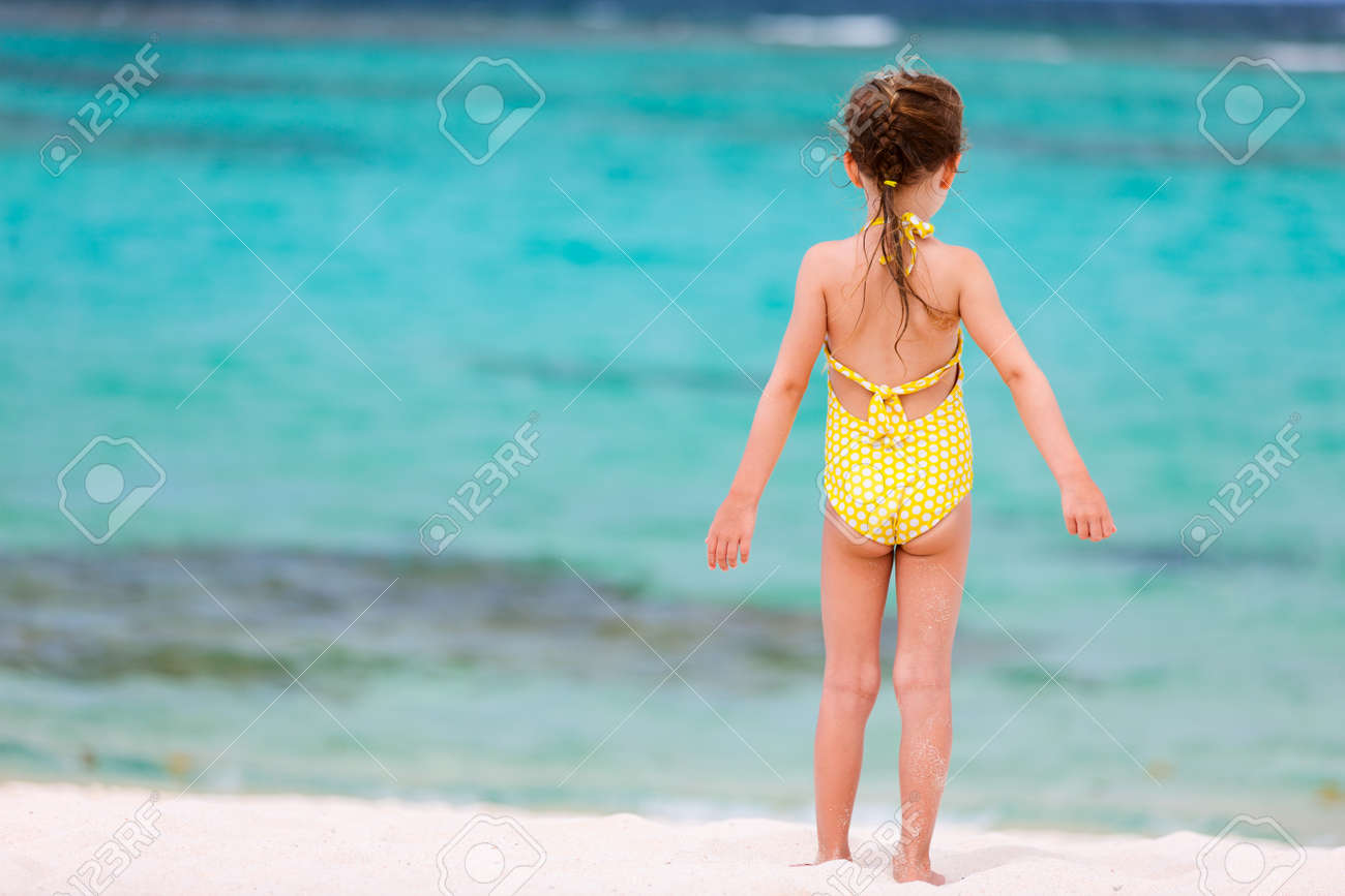 Little girl in bikini rear view Back view of a little girl at beach during summer vacation Stock Photo -  58845234