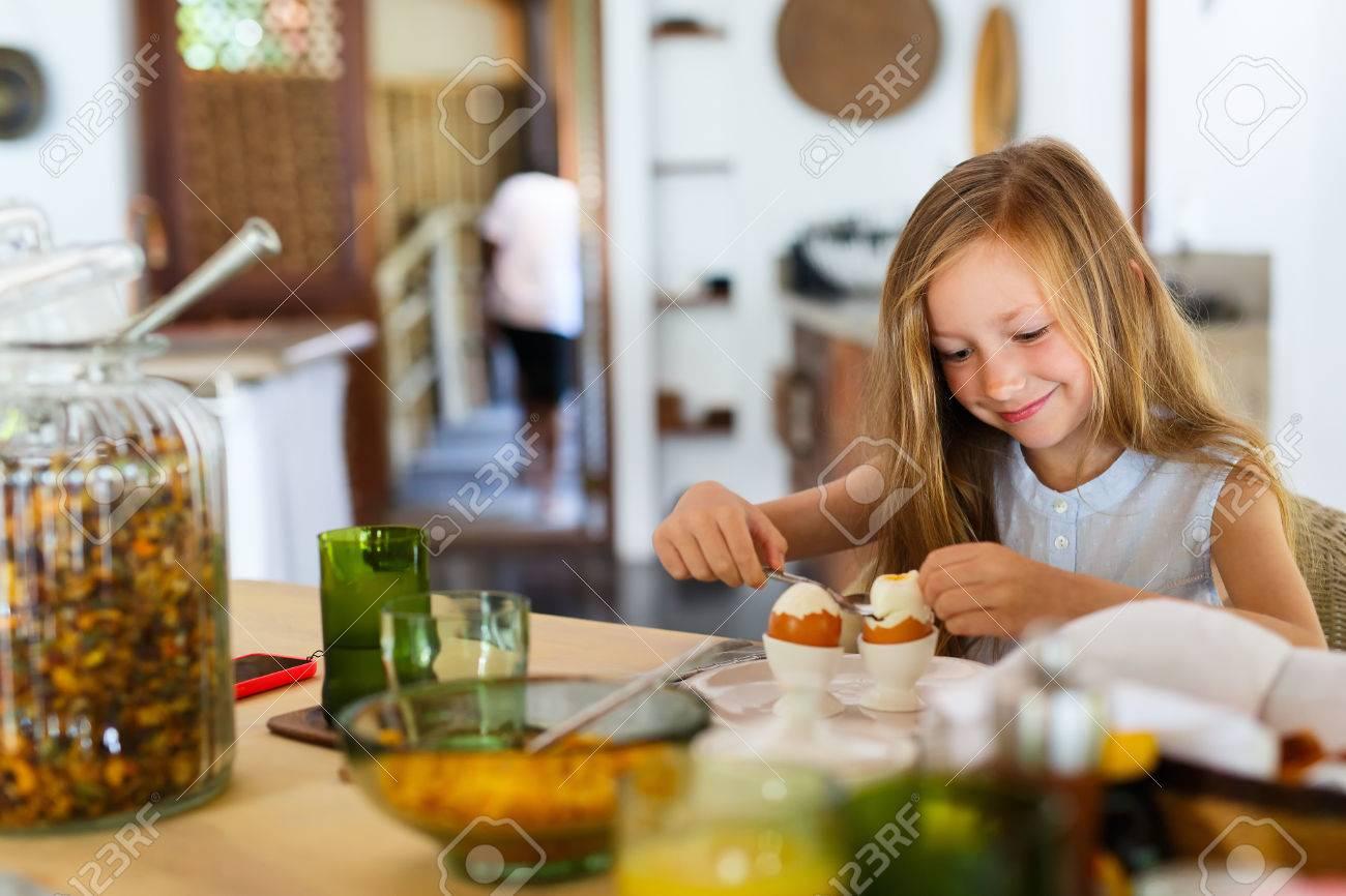 Adorable little girl eating boiled egg for a breakfast in restaurant - 63982107