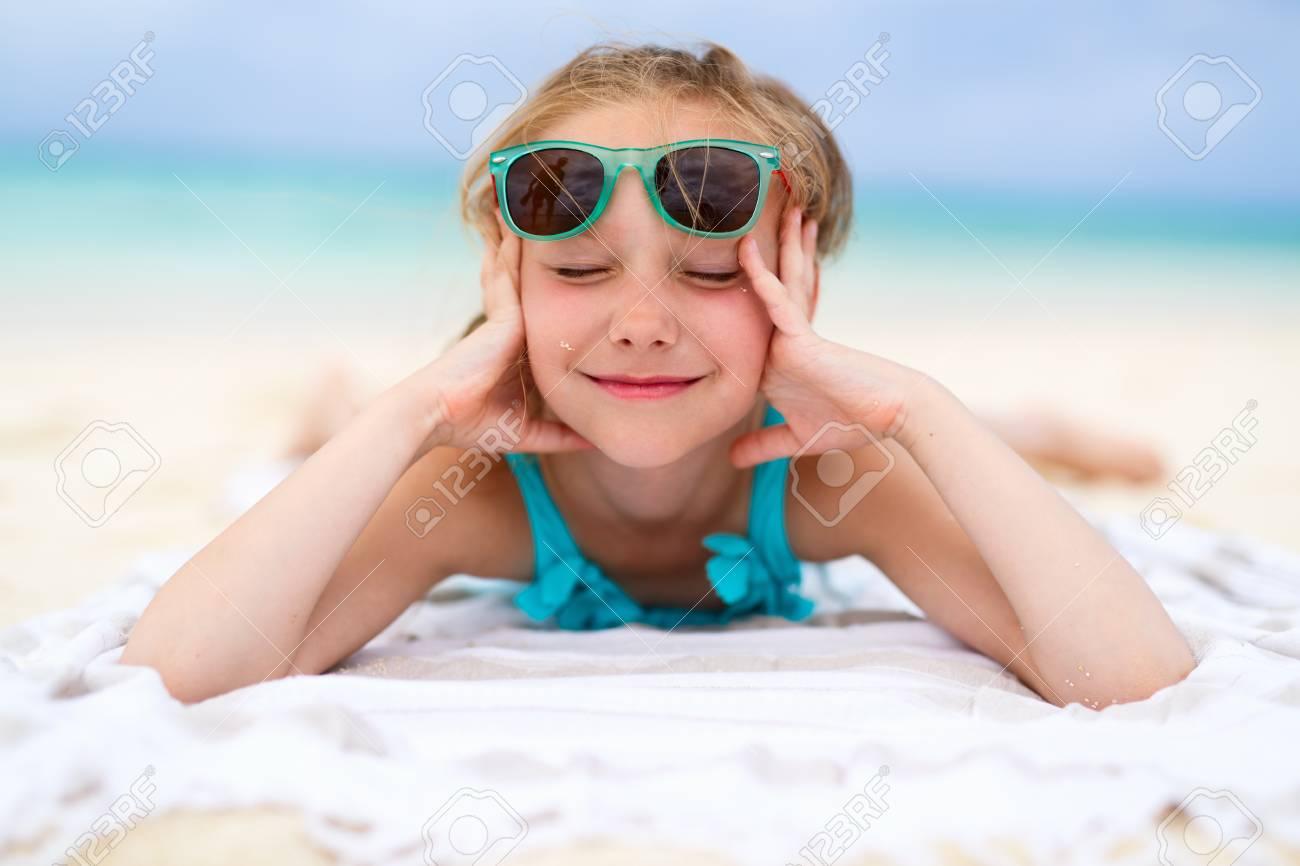 Adorable Petite Fille Couchée Sur Une Serviette De Plage Pendant Les ...