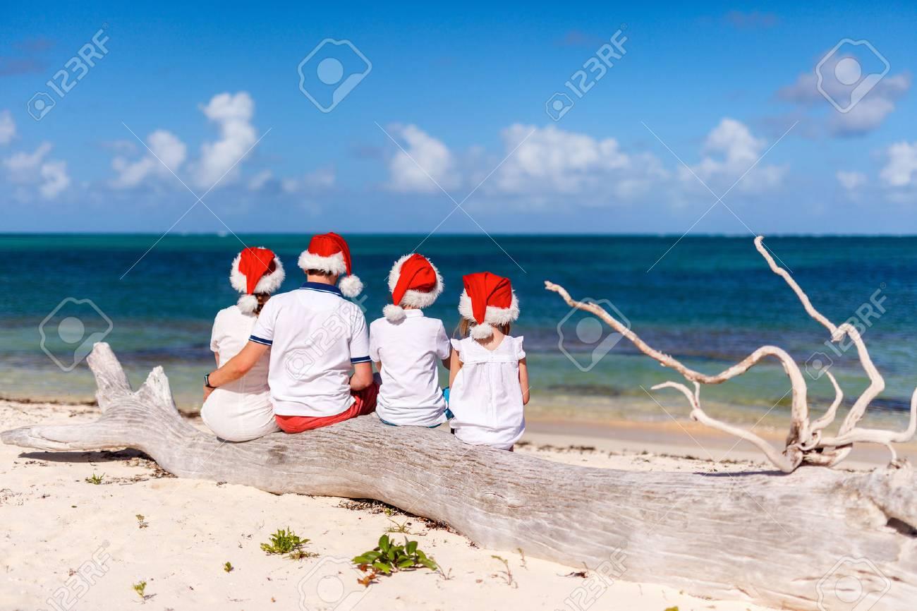 Back view of beautiful family wearing red Santa hats at tropical beach celebrating Christmas - 66594504