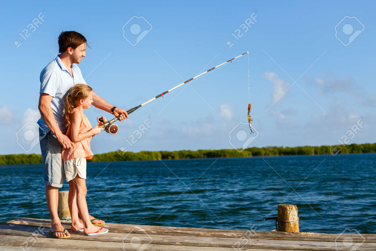 Family father and daughter fishing together from wooden jetty - 77385779