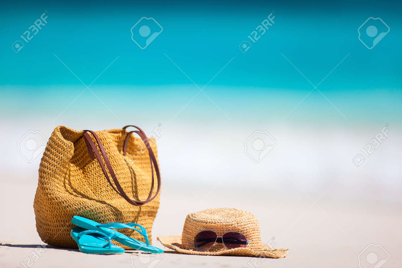 Straw hat, bag, sun glasses and flip flops on a tropical beach - 80101326