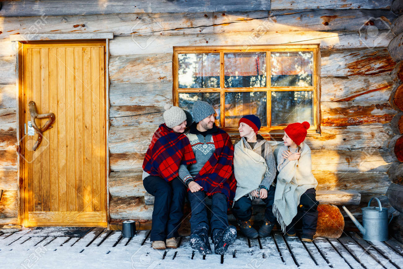 Family with kids outdoors on beautiful winter day in front of log cabin vacation house - 87332378
