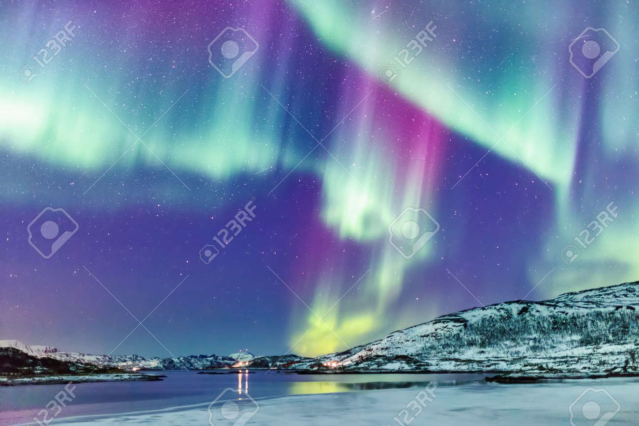 Incredible Northern lights Aurora Borealis activity above the coast in Norway - 97962338