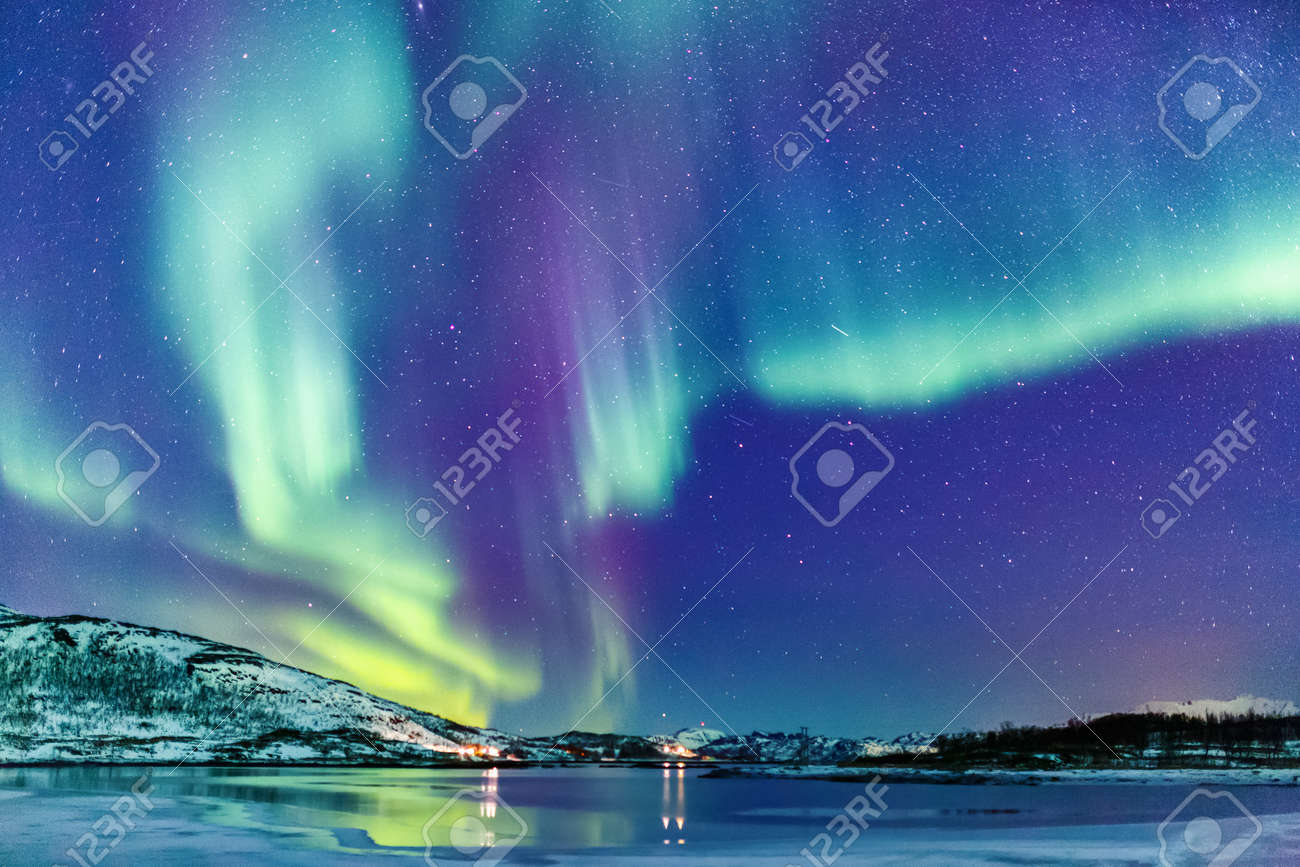 Incredible Northern lights Aurora Borealis activity above the coast in Norway - 99049388