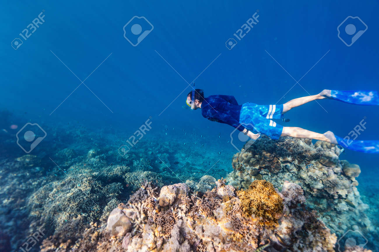 Underwater photo of a young man snorkeling free diving at coral reef in tropical ocean - 99049468