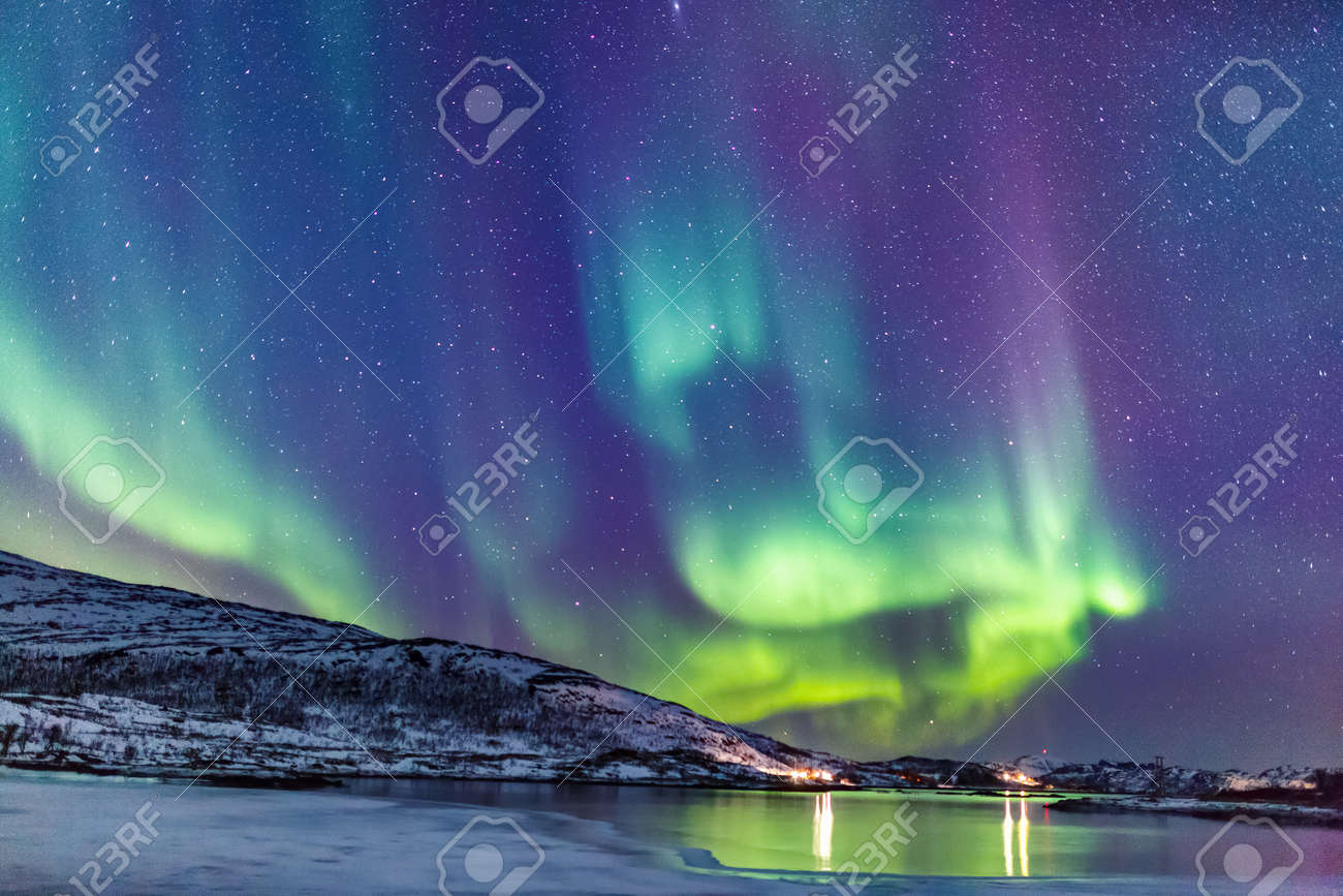 Incredible Northern lights Aurora Borealis activity above the coast in Norway - 99017800