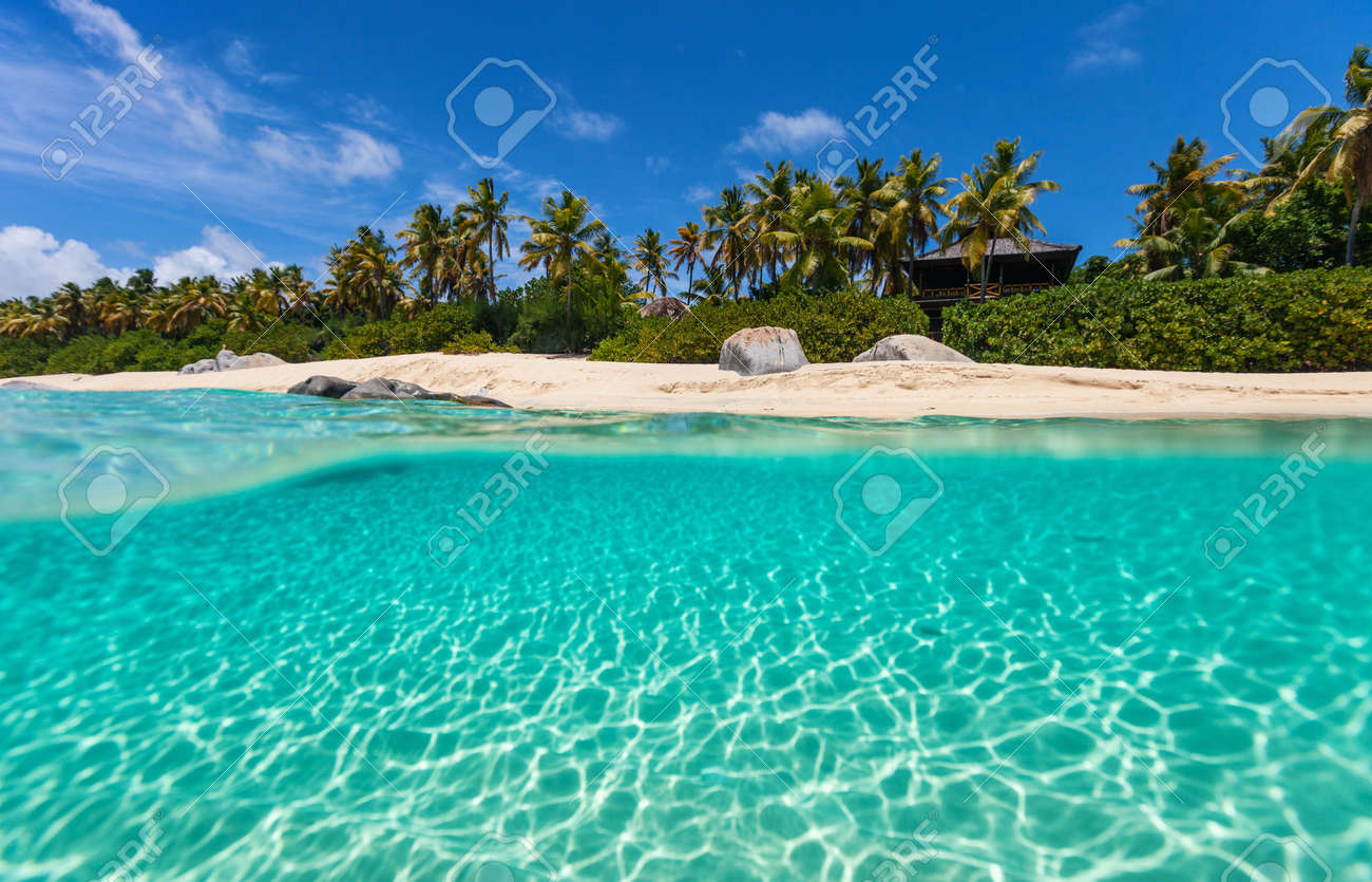 Beautiful tropical beach with white sand, turquoise ocean water and blue sky at Virgin Gorda, British Virgin Islands in Caribbean - 99862006