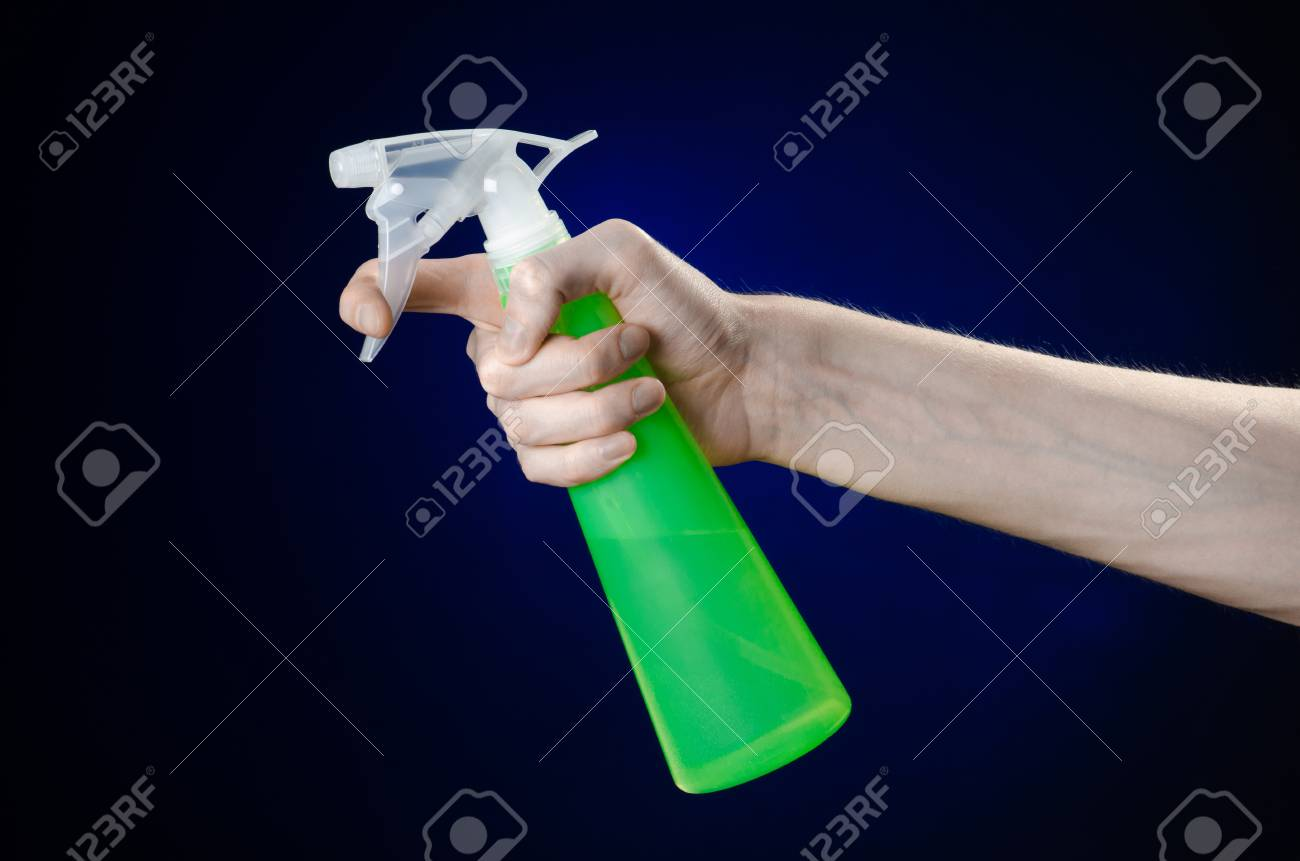 Cleaning the house and cleaner theme: man's hand holding a green