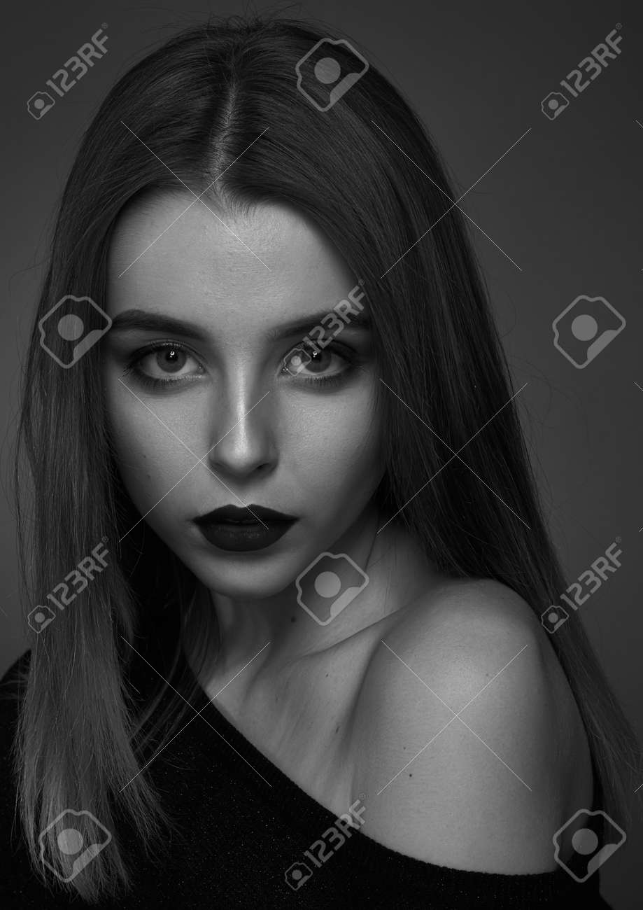 Dramatic black and white portrait of a beautiful girl on a dark