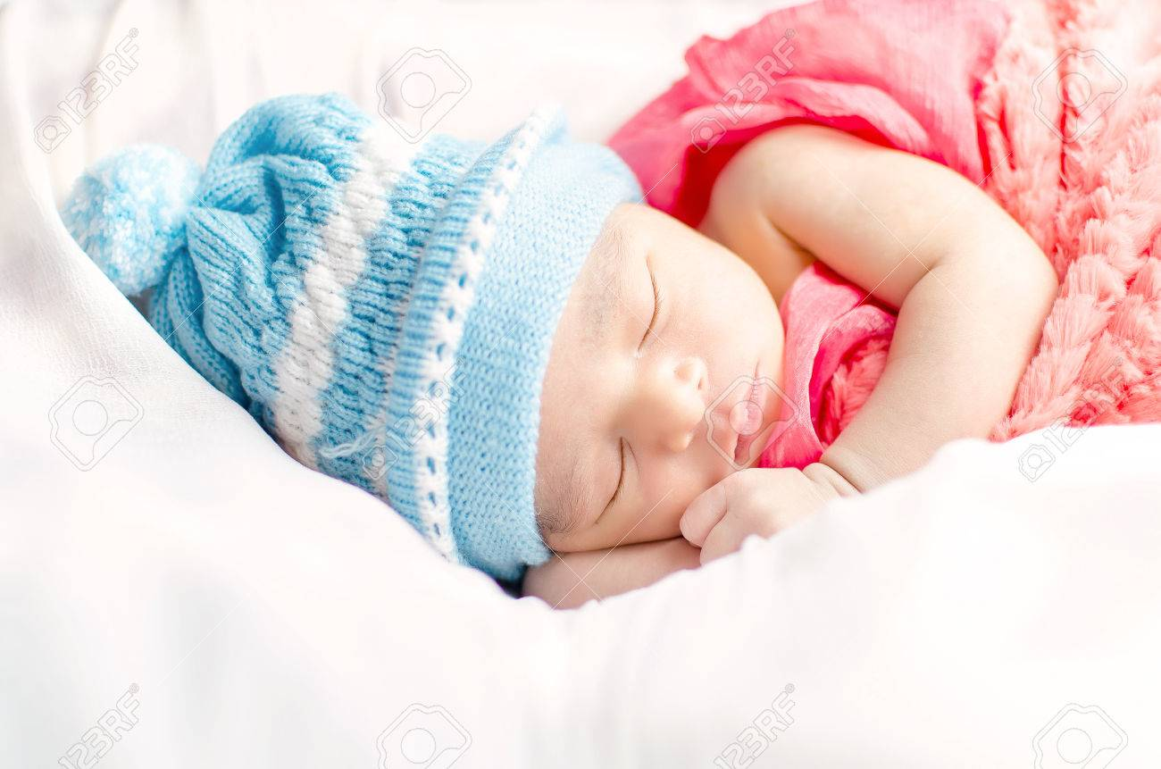Newborn baby boy sleeping in basket wearing blue hat and red blanket  isolated in white background eb470918ff6b