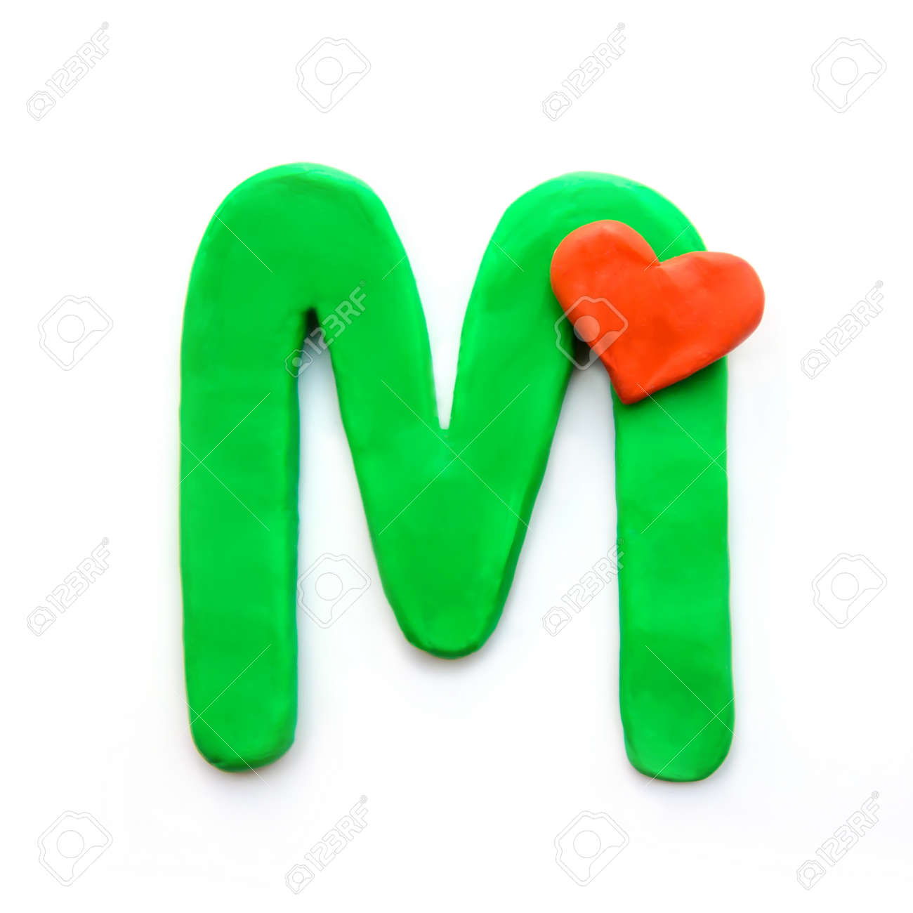 Green plasticine letter M English alphabet with red heart meaning