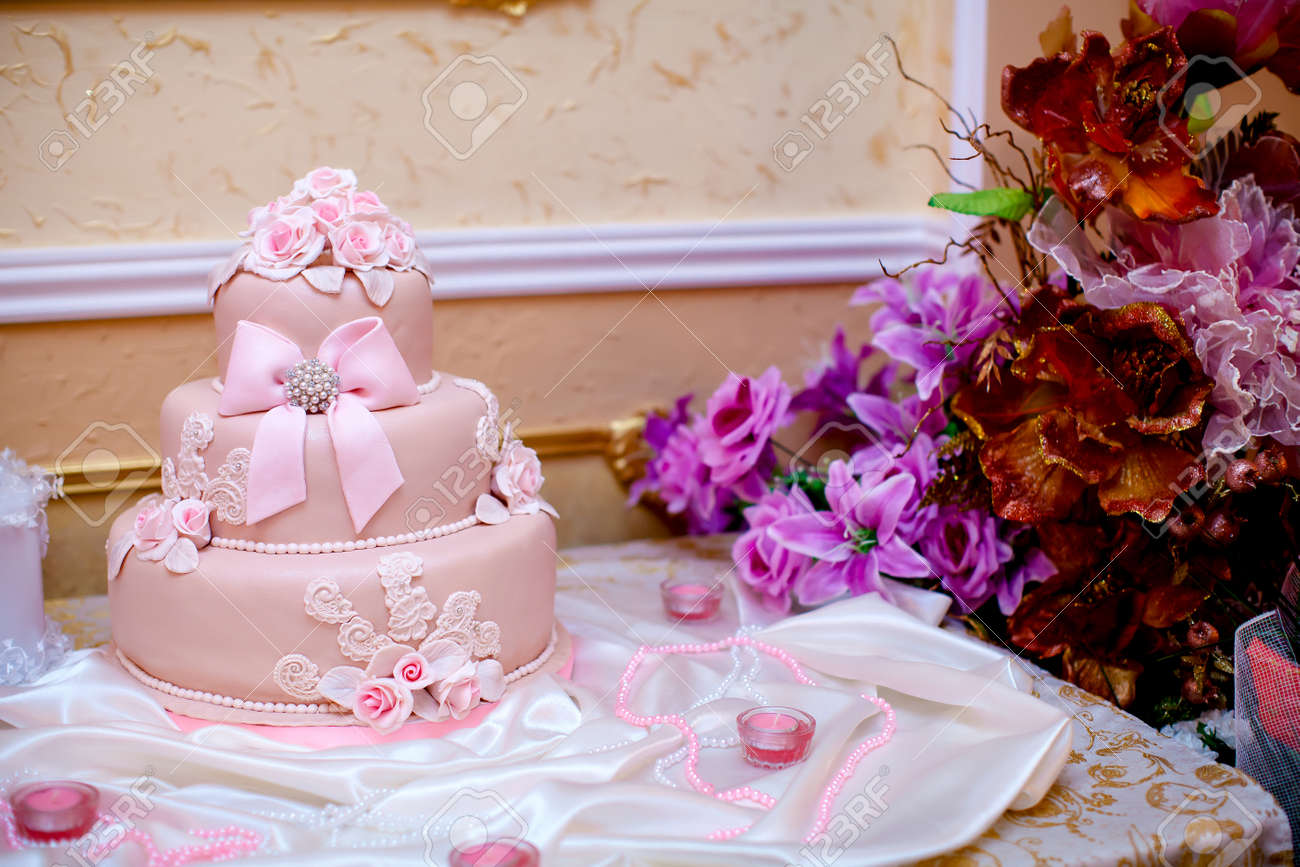 Pink Wedding Cake With Flower On Desk Stock Photo, Picture And ...