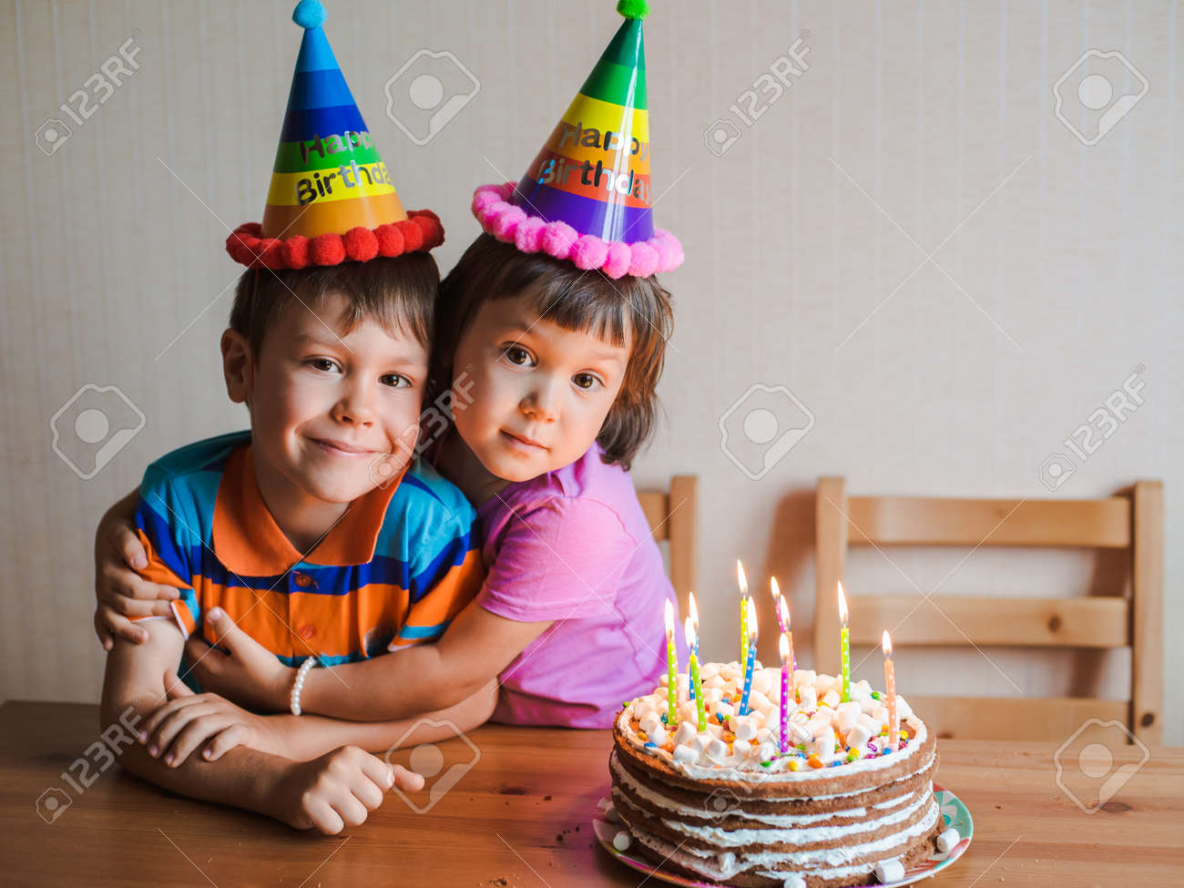 Brother and sister are eating a birthday cake and hugging  Childrens