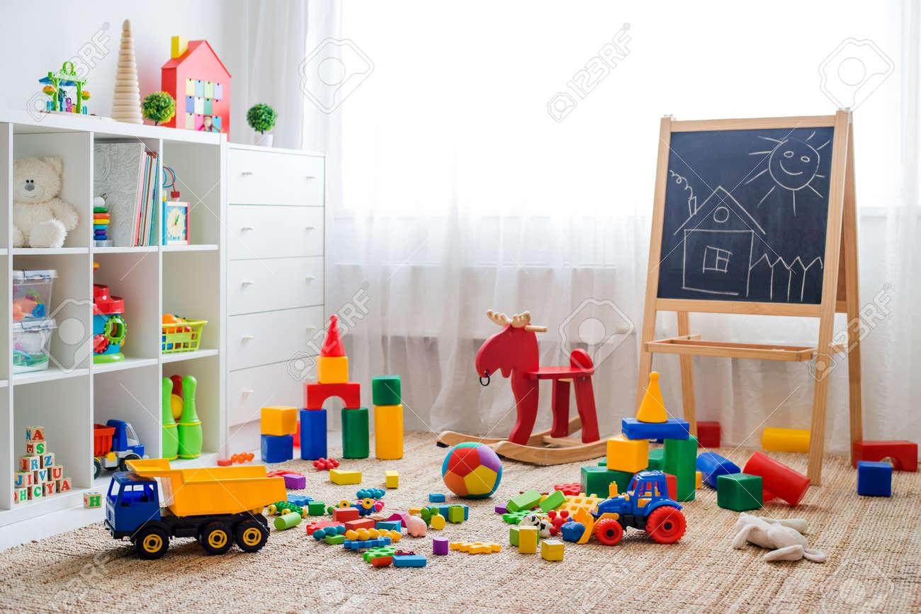 Children's playroom with plastic colorful educational blocks toys. Games floor for preschoolers kindergarten. interior children's room. Free space. background mock up chalkboard - 119054817