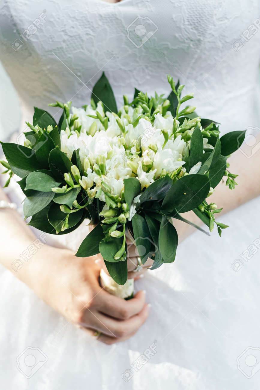 Beautiful wedding bouquet of white freesia flowers in brides beautiful wedding bouquet of white freesia flowers in brides hand stock photo 64135805 izmirmasajfo
