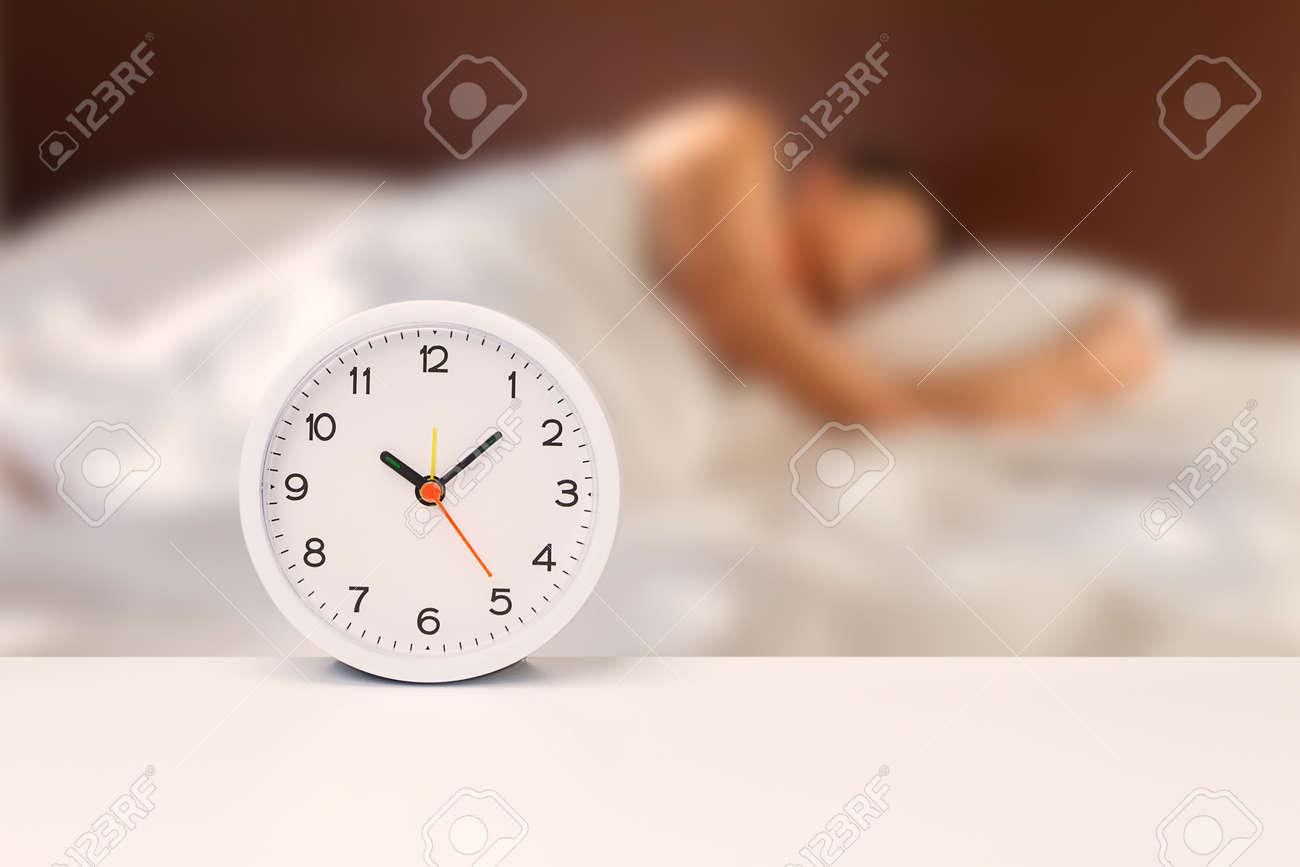 Réveil blanc sur un bureau blanc sur un homme flou dormir sur une