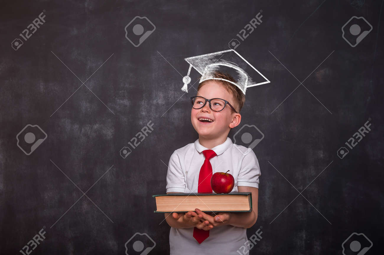 Smart educated school kid student with graduation hat doodle picture on chalkboard. little boy with paintbrush creative drawing light bulb ideas on wall. - 153581669