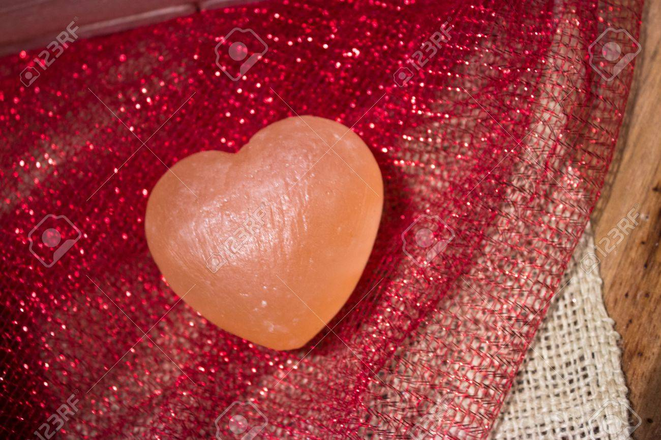 Pink Himalayan sea salt heart on red sparkly fabric and white burlap Stock Photo - 17709706