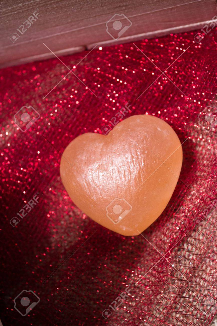 Pink Himalayan sea salt heart on red sparkly fabric and white burlap Stock Photo - 17709687
