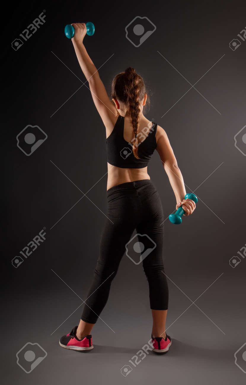 little girl in sportswear engaged with small dumbbells on a dark background - 123922440