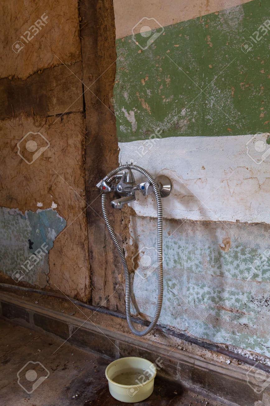 ein alter wasserhahn auf einem absolut marode bad wand mit einer