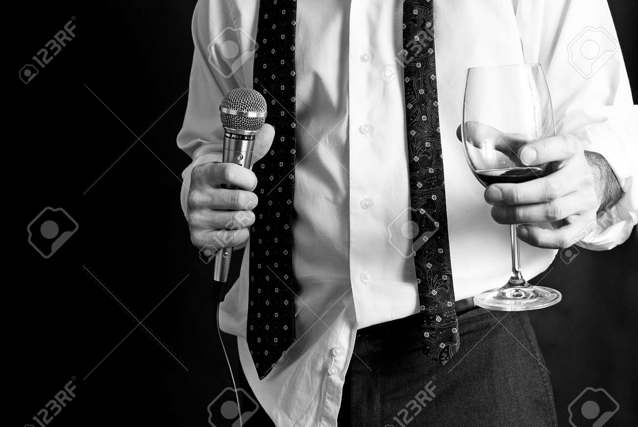 Image of a man holding a microphone and a drink dressed nicely - 11961754