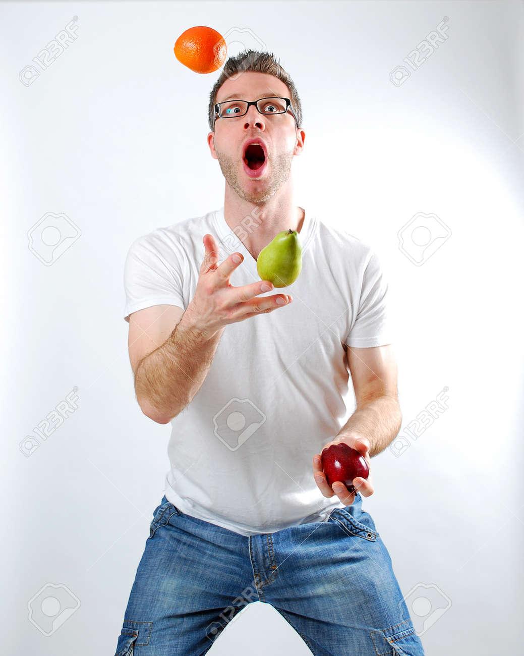 Image of a man juggling fruit - 13385006