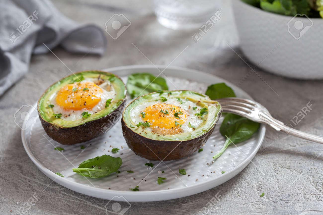 Healthy breakfast. Avocado stuffed with eggs - 95277355