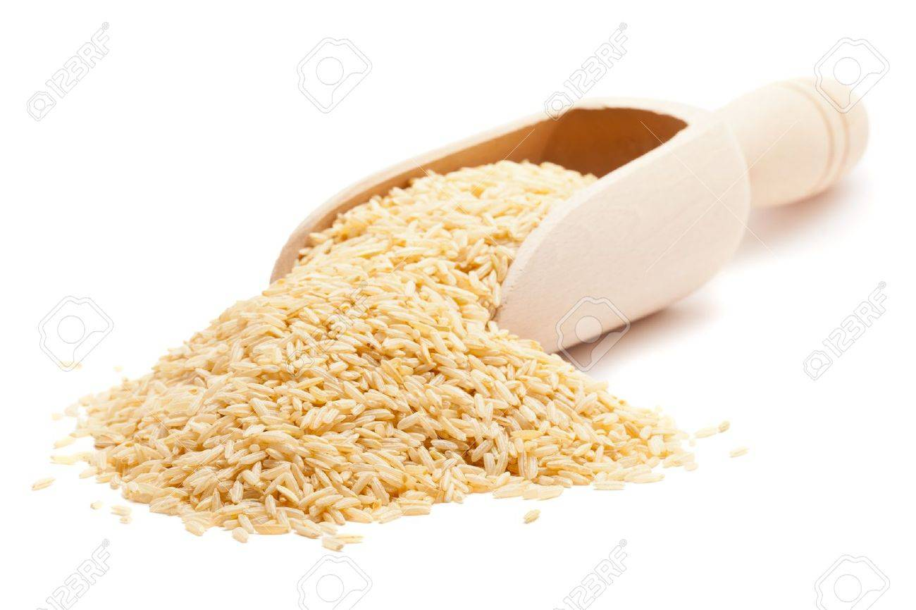 Raw organic brown rice in wooden scoop over white background Stock Photo - 10800970