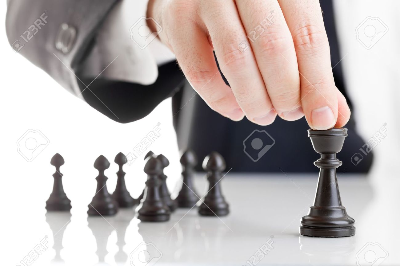 Business man moving chess figure with team behind - strategy or leadership concept Stock Photo - 12066752
