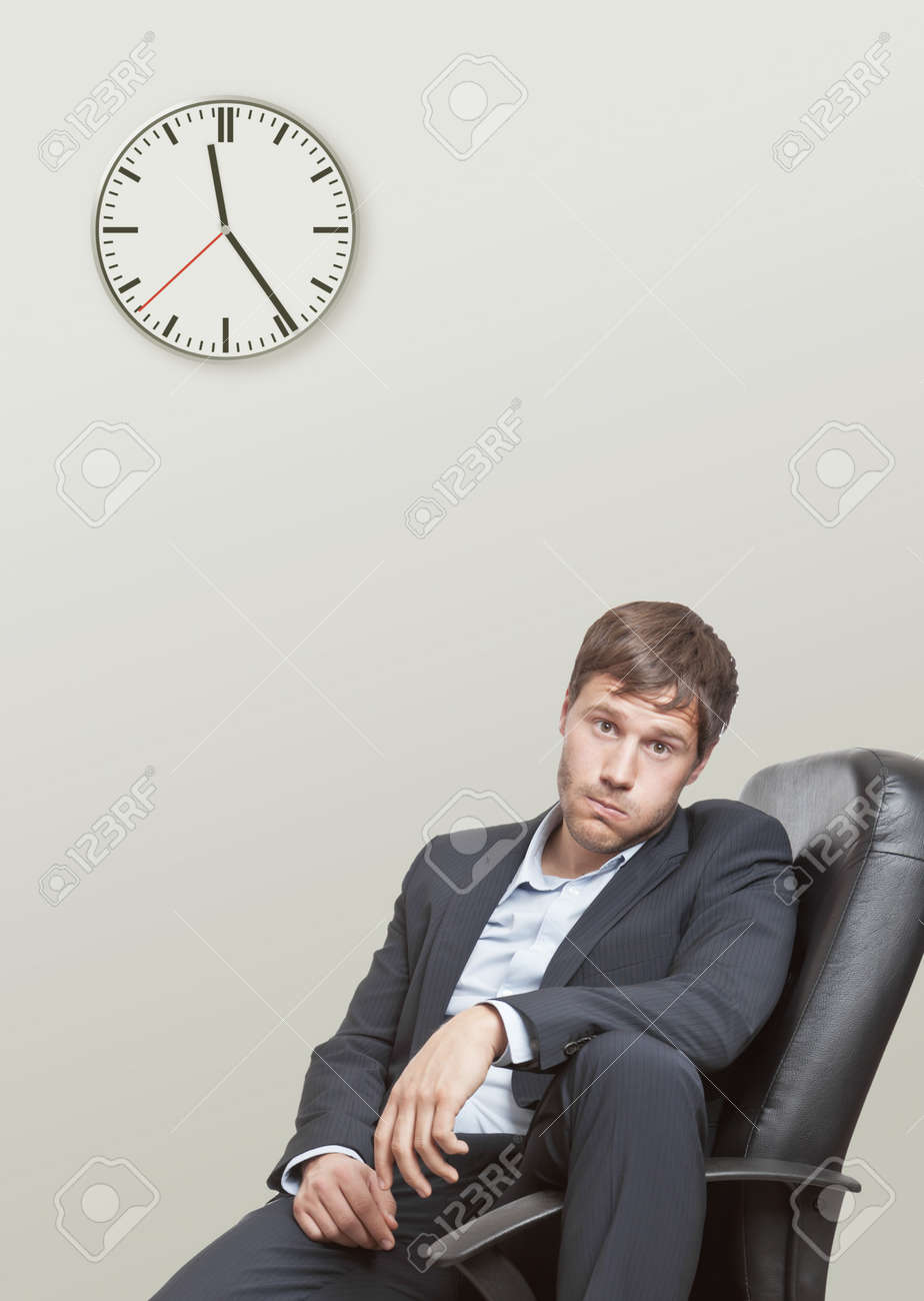 Frustrated young business man waiting for the end of the workday Standard-Bild - 14433305