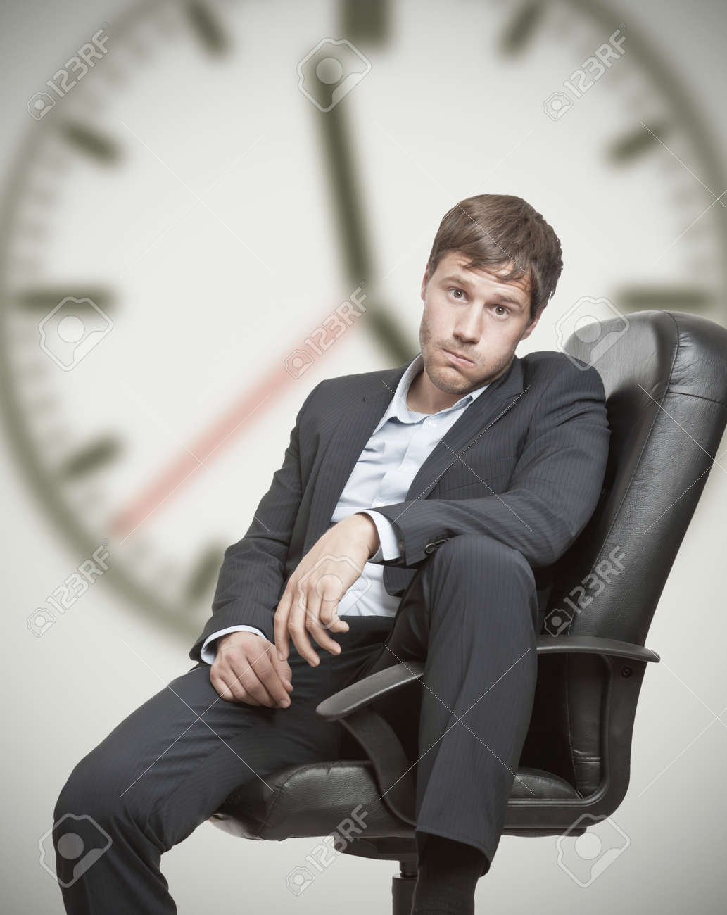 Frustrated young business man waiting for the end of the workday Standard-Bild - 14433306