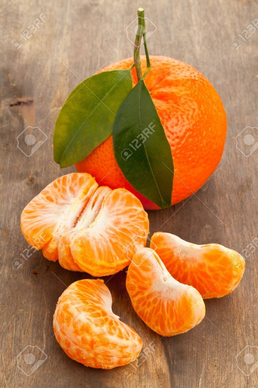 Organic mandarin whole and slices on wooden table Standard-Bild - 17625234