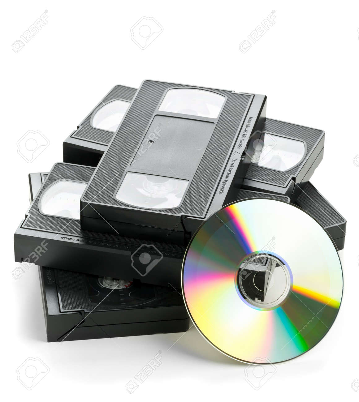 Heap of analog video cassettes with DVD disc - old movies backup or transfer concept Standard-Bild - 43609334