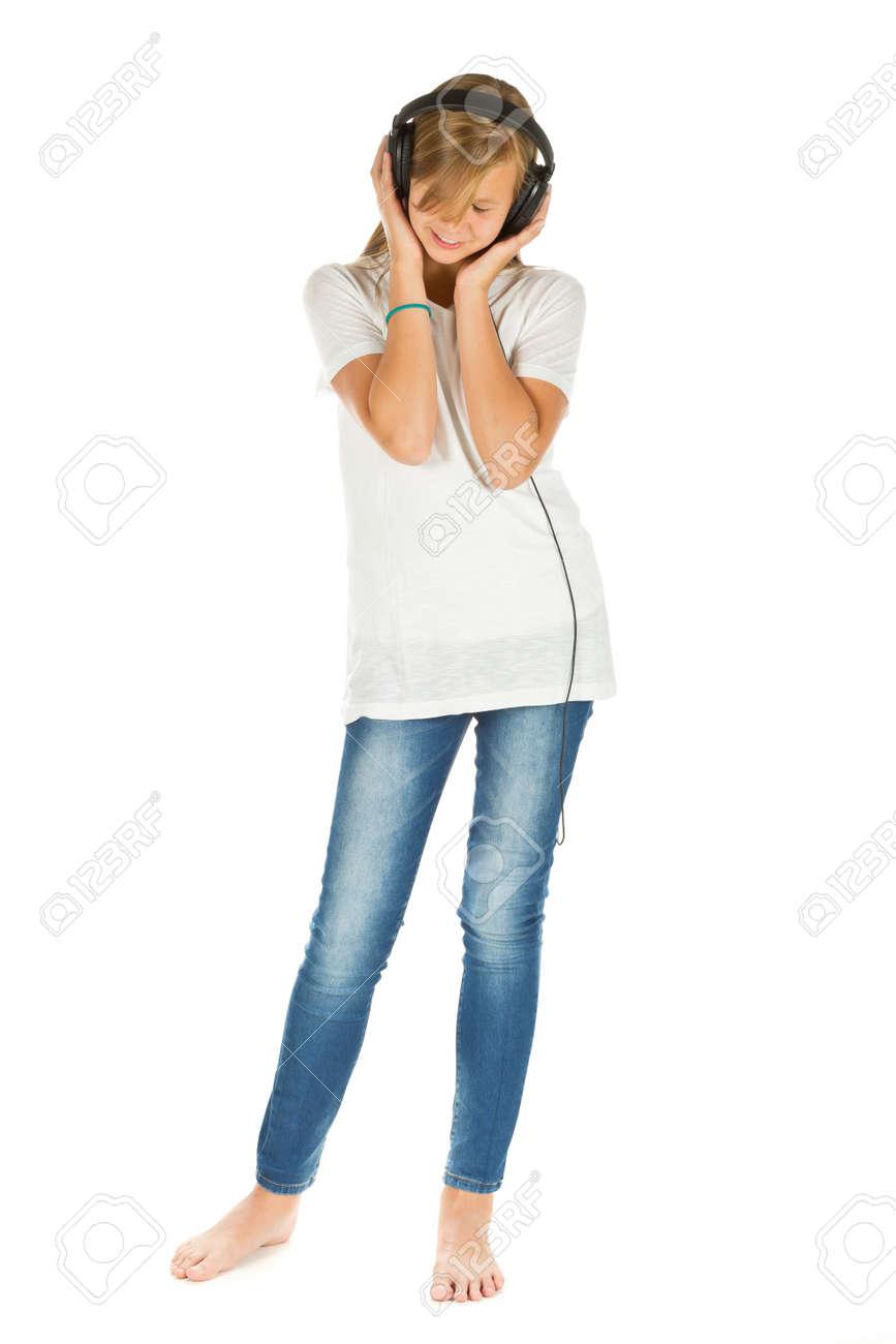 Jeune Fille écoute Debout à La Musique Avec Un Casque Sur Fond Blanc